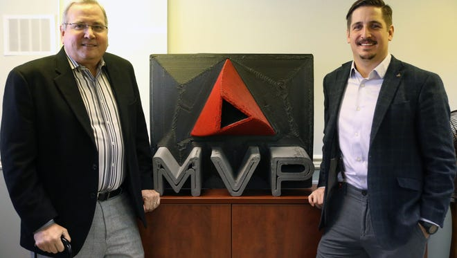 Peter Hedger and Peter Hedger Jr. of Magnum Venus Products pose in font of a 3D printed sign Thursday, Dec. 15, 2016, after their announcement of the company's expansion, which will include a new manufacturing plant in Knoxville, creating 70 jobs.