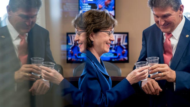 Sen. Susan Collins, R-Maine, left, and Sen. Joe Manchin, D-W.Va., right, clink glasses in a toast to each other as they wait to speak at a news conference on Capitol Hill in Washington, Monday, Jan. 22, 2018, after senators reached an agreement to advance a bill ending government shutdown. Collins and Manchin were also involved in the bipartisan efforts to compromise on immigration legislation.