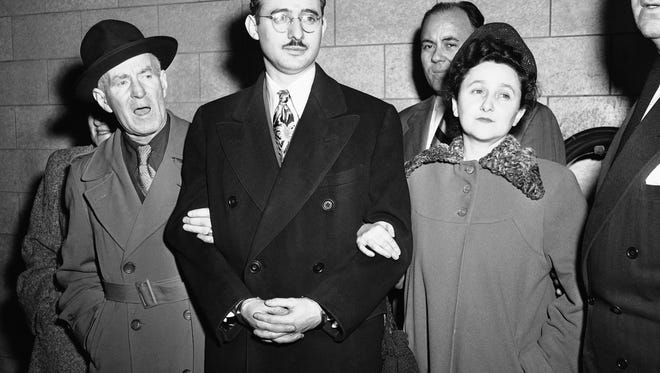 FILE - In this March 8, 1951 file photo from left, Harry McCabe, Deputy U.S. Marshall; Julius Rosenberg and wife, Eithel Rosenberg and Anthony H. Pavone, Deputy U.S. Marshall in New York. Julius Rosenberg, 33-year old electrical engineer from New York City and his wife were on trial on charges of conspiracy to commit espionage during World War II, involving U.S. atomic secrets.  The sons of convicted spy Ethel Rosenberg are asking President Barack Obama to exonerate their mother. Michael and Robert Meeropol were presenting a letter at the White House on Thursday, citing unsealed court records they say cast doubt on their mother's guilt.  (AP Photo)