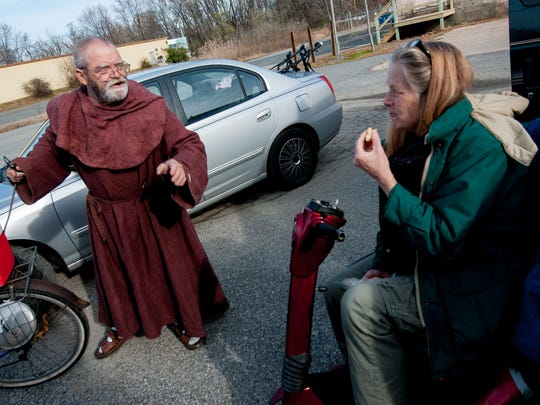 Brother George Algard offers inspiring words to Carla Stewart-Kessler of Perryville, Maryland, as he hands out warm food Sunday to those in need behind the Paris Foundation in Elkton, Maryland, as he does every week. Stewart-Kessler says she would never miss a Sunday.