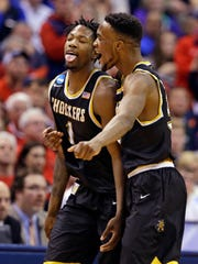 Wichita State forward Zach Brown (1), left, and forward Markis McDuffie (32) celebrate during the second half of a first-round game against Dayton in the men's NCAA college basketball tournament in Indianapolis, Friday,