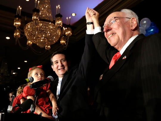 Ted Cruz, left, raises his hand with his father Rafael,