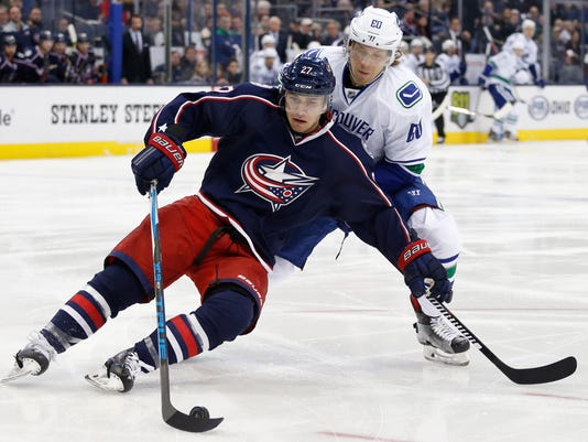 Columbus Blue Jackets' Ryan Murray, left, tries to control the puck as Vancouver Canucks' Markus Granlund, of Finland, defends during the first period of an NHL hockey game Thursday, Feb. 9, 2017, in Columbus, Ohio. (AP Photo/Jay LaPrete)