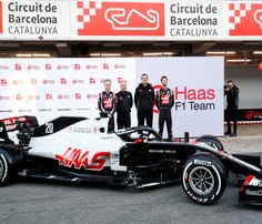 Kevin Magnussen, left, and Romain Grosjean, right, stand with other officials after unveiling the Haas VF-20 ahead of the Formula One pre-season testing session at the Barcelona Catalunya racetrack in Montmelo, outside Barcelona, Spain, Wednesday, Feb. 19, 2020. (AP Photo/Joan Monfort)