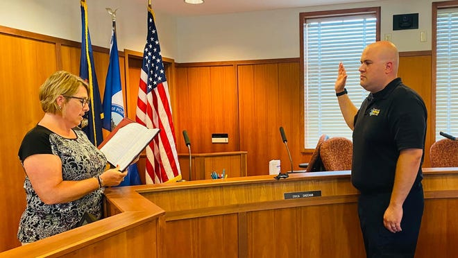 Portland City Clerk Nikki Miller (left) swears in Zachary Waltersdorf as the incoming director of Portland Ambulance.