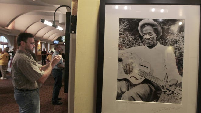 Jeff Harris of Rochester looks over the legendary photographs of Son House taken by Dick Waterman that are on display at the Journey to the Son: A Celebration of Son House at Geva Theatre Center in Rochester.