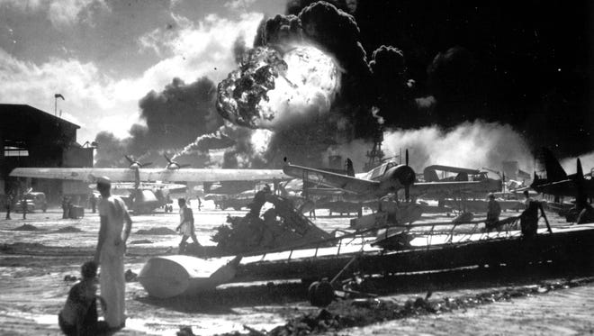 In this image provided by the U.S. Navy, sailors stand among wrecked airplanes at Ford Island Naval Air Station as they watch the explosion of the USS Shaw in the background, during the Japanese surprise attack on Pearl Harbor, Hawaii, on December 7, 1941.