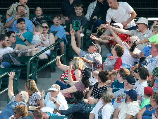 Red Wings fans reach for a ball during the game against Pawtucket in the eighth inning at Frontier Field. Paying attention to the game is a fan's responsibility to avoid being struck by foul balls, but team is expanding safety netting behind dugouts for fans in those sections.