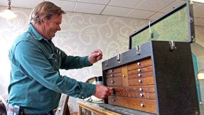 Backroads Antiques co-owner George Schweier looks through an antique tool box on Tuesday at his store on Main Avenue in Aztec.