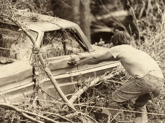 A man fights through debris and attempts to open a car door in the aftermath of the July 31, 1976 Big Thompson Flood. Once the water receded, mud and debris forced a yearslong cleanup and rebuilding effort.
