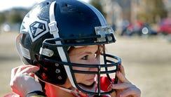 In this Feb. 12, 2014, photo, Jen Welter puts her helmet