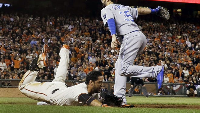 San Francisco Giants' Gregor Blanco is out at first as he dives with Kansas City Royals' Eric Hosmer covering during the seventh inning of Game 3 of baseball's World Series Friday, Oct. 24, 2014, in San Francisco. (AP Photo/David J. Phillip)