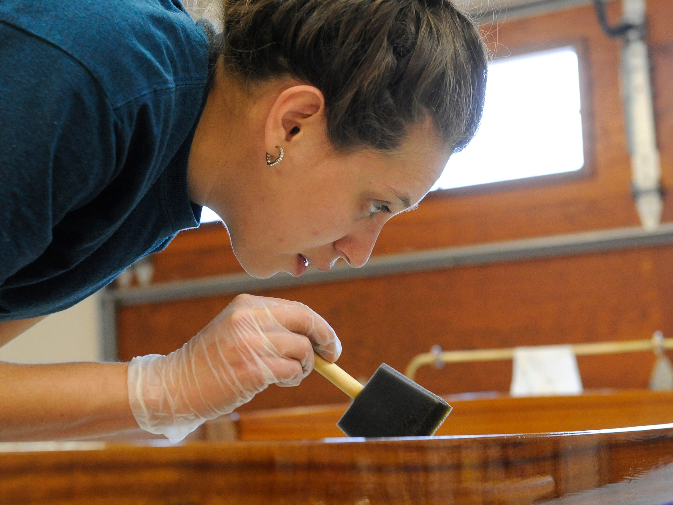 Angela Stober is meticulous as she applies fine varnish