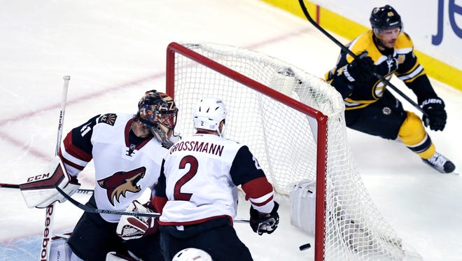 Arizona Coyotes goalie Mike Smith, left, looks back at the puck as Boston Bruins center David Krejci, of the Czech Republic, right, skates past after his goal during the first period of an NHL hockey game in Boston, Tuesday, Oct. 27, 2015.