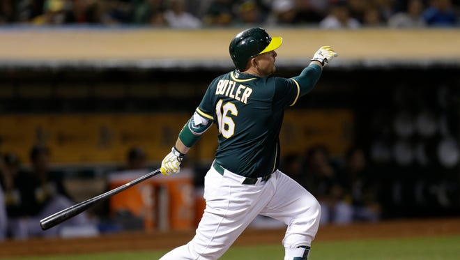 Oakland Athletics' Billy Butler watches his RBI sacrifice fly against the Boston Red Sox during the fourth inning of a baseball game Friday, Sept. 2, 2016, in Oakland, Calif.