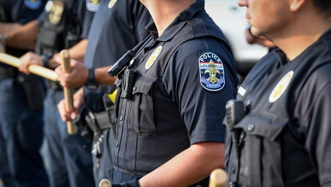 Officers stand as protesters march down Broadway as part of a Black Lives Matter rally in Louisville, Ky., Sunday, August 13, 2017.
