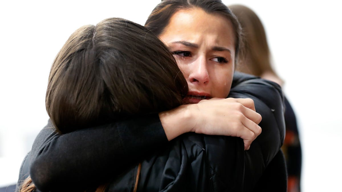 Bailey Kowalski hugs a friend before a news conference in East Lansing, Mich., Thursday, April 11, 2019. The 22-year-old Michigan State University student is speaking publicly a year after suing the school, alleging that three former men's basketball players raped her in 2015 and that she was discouraged by counseling center staff from reporting what happened. (AP Photo/Paul Sancya)