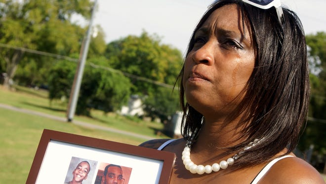 Alicia Wilson, whose son Rameon Wilson was murdered in April 2013, holds a picture of him following a balloon release in his memory on what would have been his 24th birthday in September 2013.