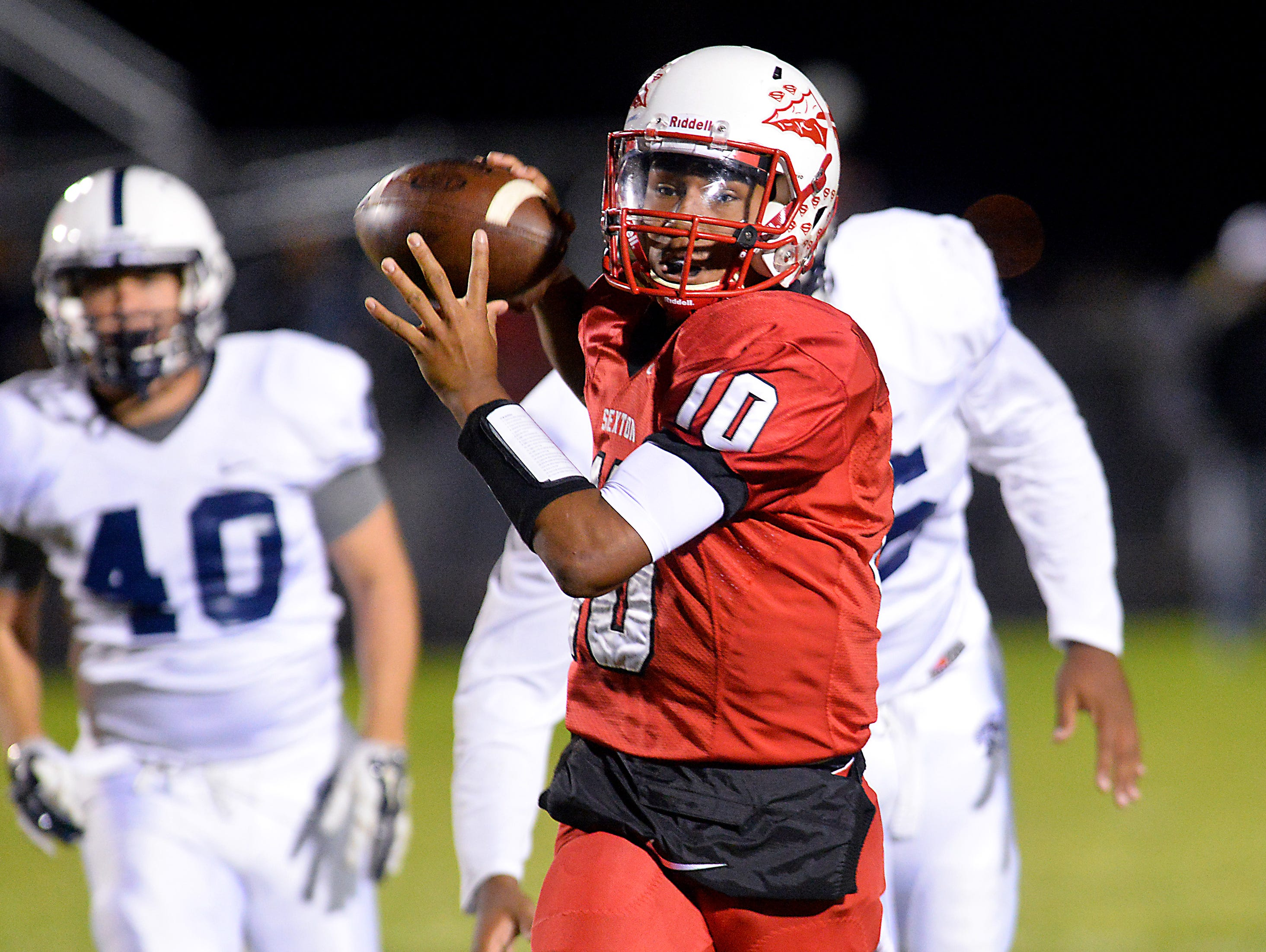 Sexton quarterback Mike Lynn III escapes East Lansing defenders and passes on the run at Sexton Friday.