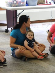 Abigail Hornbaker, 14 months, sits on her mother's (Kellie Hornbaker) lap during the Music Together of Galloway class at the Mays Landing library.
