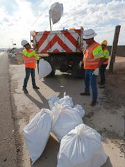 A Texas Department of Transportation crew loads bags