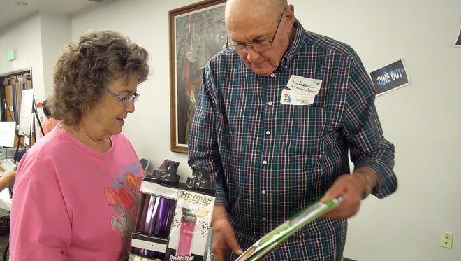Encore volunteer Larry Brewer, right, passes on a prize to a lucky winner at the 2015 Encore Birthday Party. The program will host its 13th Annual Birthday Party on Aug. 5.