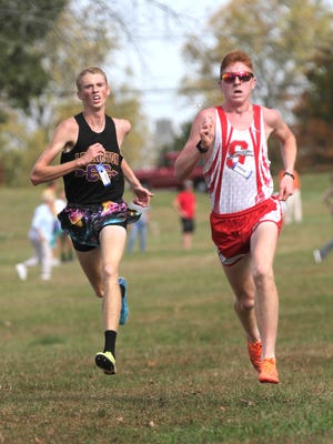Lexington's Kyle Johnston and Shelby's Caleb Brown cross the finish line during district cross country at Galion on Saturday.