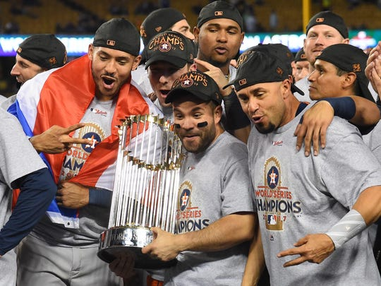 Nov 1, 2017; Los Angeles, CA, USA; Houston Astros second baseman Jose Altuve (center) celebrates with teammates with the Commissioner's Trophy after defeating the Los Angeles Dodgers in game seven of the 2017 World Series at Dodger Stadium. Mandatory Credit: Jayne Kamin-Oncea-USA TODAY Sports