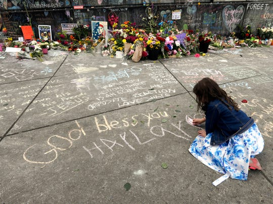 Haylay Hanson colors in a chalk heart next to her name in Portland, Ore., Wednesday, May 31, 2017, at a memorial for the two men fatally stabbed on a light rail train in Portland last week. The man charged with fatally stabbing the two men and injuring a third who tried to shield young women from an anti-Muslim tirade, appeared to brag about the attacks as he sat in the back of a police patrol car according to court documents.(AP Photo/Don Ryan)