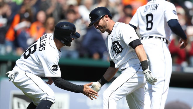 Tigers centerfielder Andrew Romine, right, celebrates with Tyler Collins after hitting a grand slam against the Twins during the fourth inning Wednesday, April 12, 2017 at Comerica Park in Detroit.