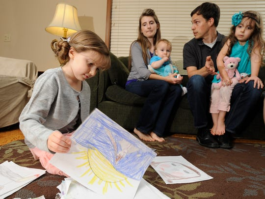 Spresa Carroccio looks over some of her drawings while her family looks on.