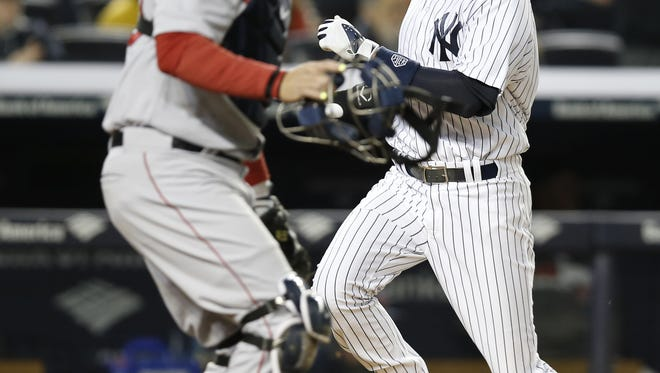 Boston Red Sox catcher A.J. Pierzynski, left, reacts as the Yankees' Derek Jeter scores on Jacoby Ellsbury's fifth-inning  single  at Yankee Stadium Thursday night.  The Yankees defeated the Red Sox 4-1.