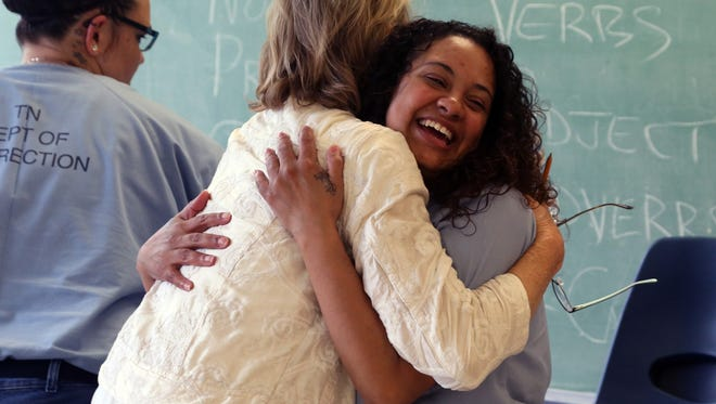 Kelly Hyman, right, an inmate at the Tennessee Prison for Women and a participant in the Building Entrepreneurs for Success in Tennessee program, is embraced by Mary Brennan, a BEST instructor, following program members' pitching of business plans.