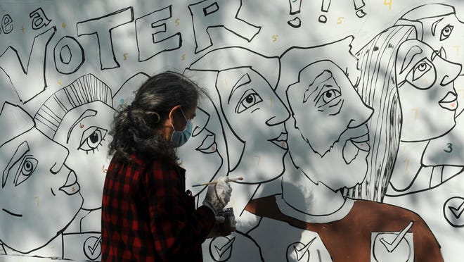 Helen Woodward, of Falmouth, finds her mark on a paint-by-number mural that was set up at Peg Noonan Park in Falmouth by the League of Women Voters. The group hosted the event to raise voter awareness.