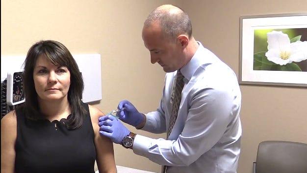 Dr. Devin Minior of Banner Urgent Care administers a flu shot on Sept. 20, 2017.