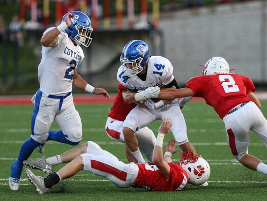 Covington Catholic's Sam Schuh is tackled by three