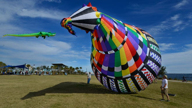 Members of the Emerald Coast Kite Flyers Club fly the Super Mega Mesh Bol kite Saturday afternoon at Community Maritime Park.