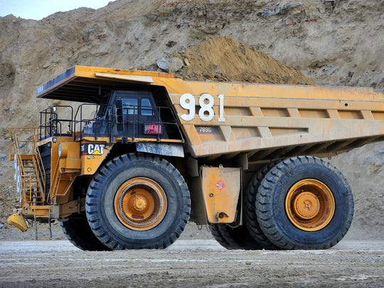 An earth-moving dump truck takes overburden away in