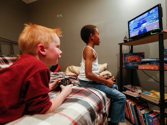 Sir Perrie Daniels, right, plays a video game with