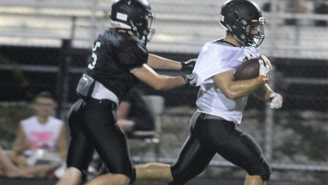 Ryle senior RB Jake Chisholm eludes a teammate for a big gain in practice Aug. 1 at Ryle.
