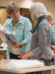 George Award winner Mary Embury helps one of the volunteers