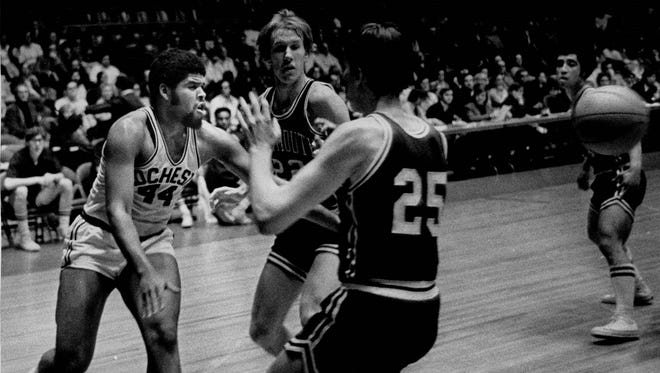 University of Rochester's Damian Upson (44) throws a pass that eludes Dartmouth's Jim Beattie and Bill Healey in a Kodak Classic matchup in 1974.