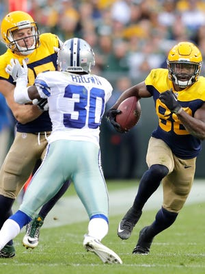 Green Bay Packers receiver Ty Montgomery runs as Jordy Nelson blocks Dallas Cowboys cornerback Anthony Brown following a reception in the second half at Lambeau Field.