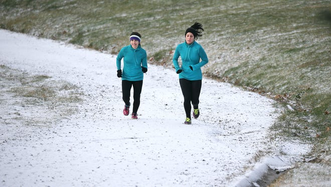 FILE PHOTO 2014: Kimberly Ball (L) and Kate Krysty of Rochester,  brave the snowfall to run the hill in Cobbs Hill Park near the reservoir as part of FIT1 exercise class.
