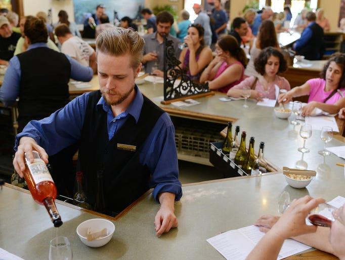 Biltmore wine server Jackson Dulaney pours wine samples for visitors in the tasting room. 7/22/14- Erin Brethauer (ebrethau@citizen-times.com)