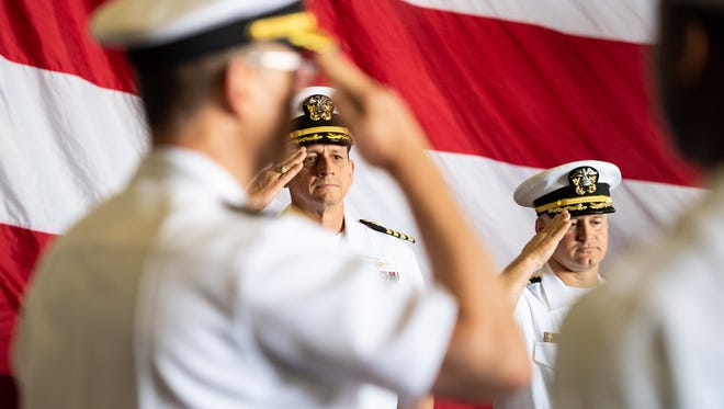 SAN DIEGO (August 3, 2018) Capt. Greg Huffman, commanding officer of the Nimitz-class aircraft carrier USS John C. Stennis (CVN 74), left, and Capt. Randy Peck, salute the colors during a change of command ceremony held in the hangar bay.