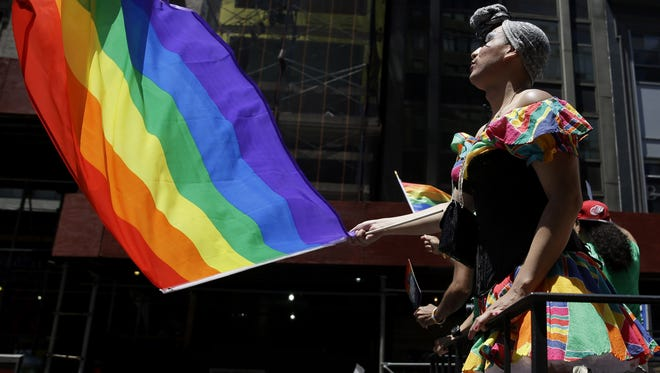 People on a float dance and wave flags during the Gay Pride Parade in New York on Sunday, June 29, 2014. Fifth Avenue became one big rainbow on Sunday, as thousands of participants waving multicolored flags made their way down the street for New York City's annual Gay Pride march.