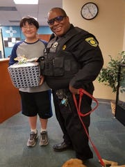 Mesilla Marshal K.C. Alberg receives an officer appreciation package from Zia Middle School student Elias Merchant.