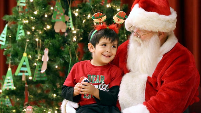 Tres Andrade meets with Santa during the ELF (Educational Learning Fair) Night on Tuesday, Dec. 6, 2016, at Oak Park Special Emphasis School in Corpus Christi.