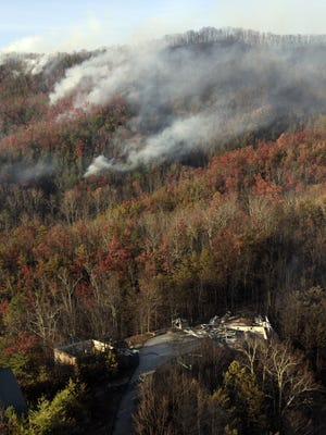 Even though forest fires scorched the Smoky Mountains, downtown Gatlinburg, Tennessee, remained largely unscathed. Buildings destroyed by a wildfire are seen among burned trees as more fires continue nearby Tuesday near Gatlinburg, Tenn.